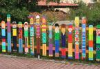 Дървена ограда боядисана като цветни човечета